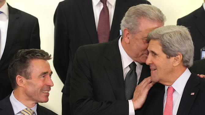 Greek Foreign Minister Dimitrios Avramopoulos, center, talks to U.S. Secretary of State John Kerry, right, and NATO Secretary General Anders Fogh Rasmussen, as they pose for a group photo, during the NATO-Russia Council during a NATO foreign ministers meeting at NATO headquarters in Brussels, Tuesday, April 23, 2013. (AP Photo/Yves Logghe)