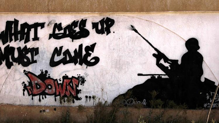 FILE --In this Saturday, Sept. 22, 2012 file photo, graffiti on one of the city walls calls on people to stop random firing of weapons making the point that when a bullet goes up it also comes down and can injure or kill people, in Benghazi, Libya. Libya's upheaval the past two years helped lead to the ongoing conflict in Mali, and now Mali's war threatens to wash back and further hike Libya's instability. There is a growing fear that post-Moammar Gadhafi Libya is becoming an incubator of turmoil, with an overflow of weapons and Islamic jihadi militants operating freely, ready for battlefields at home or abroad. (AP Photo/Mohammad Hannon, File)