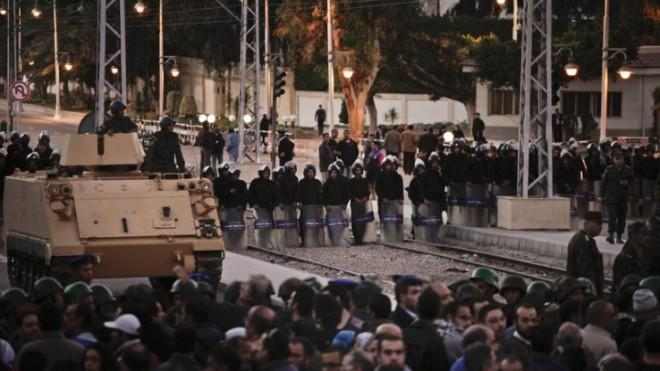 Egyptian riot police stand guard as protesters demonstrate in front of the presidential palace in Cairo on Dec. 7.