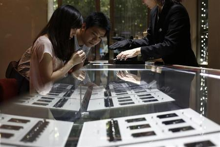 A couple selects diamond rings at a Chow Tai Fook store in Shanghai September 16, 2013. REUTERS/Aly Song/Files