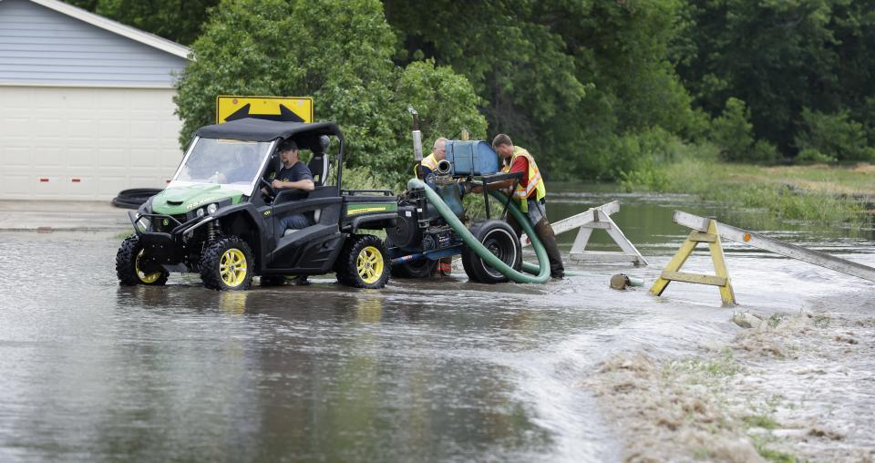 New Hartford firefighters stand in floodwaters as they work on a pump, Tuesday, June 25, 2013, in New Hartford, Iowa. Hundreds of residents obeyed an order to evacuate their homes in this northeast Iowa town Tuesday before floodwaters from a rising creek could strand them. (AP Photo/Charlie Neibergall)