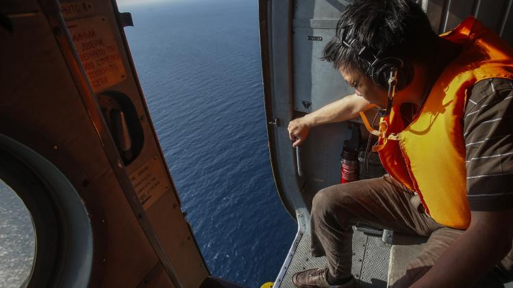 Officer looks out of a helicopter during a mission to find Malaysia Airlines flight MH370 that disappeared, near Tho Chu island