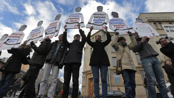 Demonstrators hold cutouts of arrested opposition activists with their photos and names during a 'March against Hatred' in St. Petersburg, Russia, Saturday, Oct. 27, 2012.  Russians are protesting against a ongoing crackdown on the opposition which was launched his spring, with arrests of activists and introduction of new harsh legislation. (AP Photo/Dmitry Lovetsky)