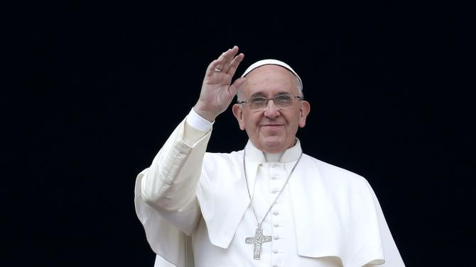 "Pope Francis waves as he delivers a ""Urbi et Orbi"" message from the balcony overlooking St. Peter's Square at the Vatican"