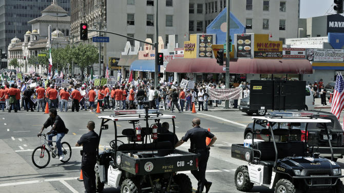 "FILE - In this Thursday, May 1, 2008 file photo, Los Angeles Police Officers stand near ""Phraselators"" as they monitor May Day protesters gathering downtown to call for immigration reform in Los Angeles. The department is using new tactics and technology, including the ""Phraselators"" which can broadcast to a crowd in different languages, in hopes of overcoming the memory of the previous year's violent event. Christopher Dorner's claim that his career as a Los Angeles police officer was undone by a racist conspiracy at the department comes at a time when it's widely held the LAPD has moved beyond the troubled racial legacy of Rodney King and the O.J. Simpson trial. (AP Photo/Ric Francis)"