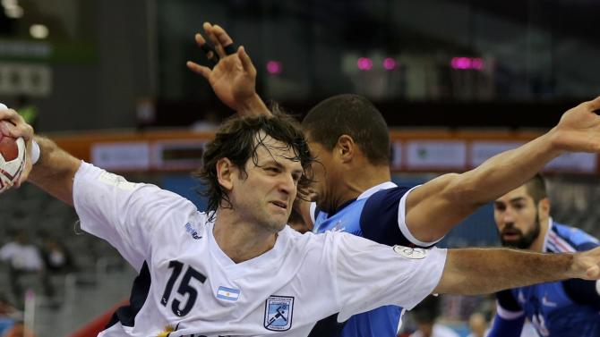 Carou of Argentina attempts to score past Narcisse of France during their round of 16 match of the 24th men's handball World Championship in Doha