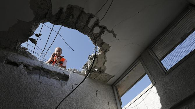 An Israeli police officer looks through a hole in the ceiling of a damaged house after a rocket fired by Palestinian militants from Gaza Strip landed in Ashkelon, southern Israel, Sunday, Nov. 18, 2012. Israel launched the operation last Wednesday by assassinating Hamas' military chief and carrying out dozens of airstrikes on rocket launchers and weapons storage sites. Over the weekend, the operation began to target Hamas government installations as well, including the offices of its prime minister. (AP Photo/Tsafrir Abayov)
