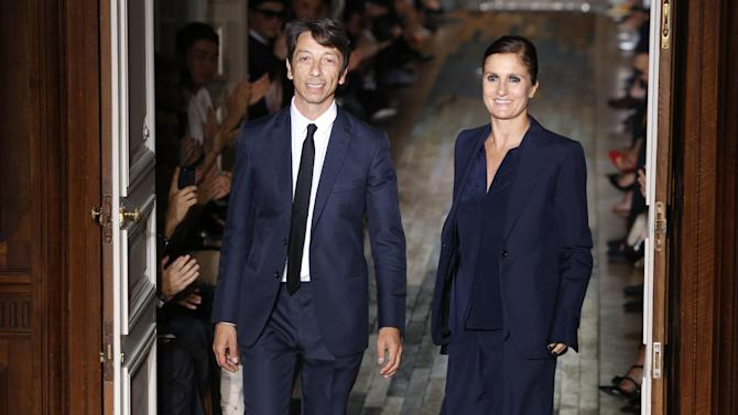 Fashion designers Maria Grazia Chiuri, right, and Pier Paolo Piccioli acknowledge applause following the presentation of the men's fashion Spring-Summer 2014 collection they designed for Valentino, Wednesday, June 26, 2013 in Paris. (AP Photo/Francois Mori)