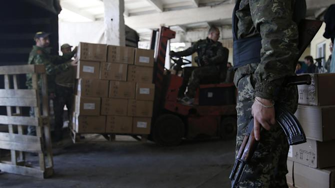 A Pro-Russian rebel guards aid delivered from Russia in the town of Donetsk, eastern Ukraine, Saturday, Sept. 20, 2014. Negotiators in Ukrainian peace talks agreed early Saturday to create a buffer zone to separate government troops and pro-Russian militants and withdraw heavy weapons and foreign fighters in order to ensure a stable truce in eastern Ukraine. (AP Photo/Darko Vojinovic)