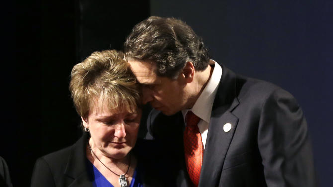 New York Gov. Andrew Cuomo embraces Janina Kaczowka, mother of slain West Webster firefighter Tomasz Kaczowka, after presenting her with a state flag during his third State of the State address at the Empire State Plaza Convention Center on Wednesday, Jan. 9, 2013, in Albany, N.Y. Kaczwoka was shot while responding to an early-morning fire in Webster, N.Y. on Dec. 24, 2012. (AP Photo/Mike Groll)