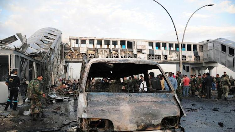 A picture released by the official Syrian Arab News Agency (SANA) on November 26, 2013 claims to shows soldiers and civilians gathering around a burnt vehicle after an alleged suicide bombing at a bus stop in Somariyeh, west of Damascus