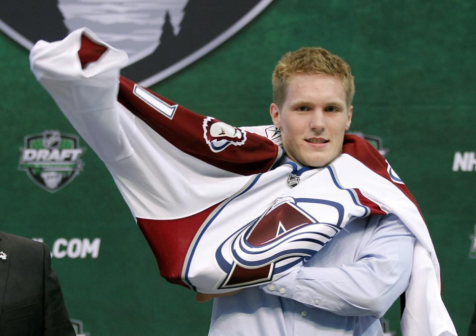 Gabriel Landeskog puts on a Colorado Avalanche sweater after he was drafted by the team in the first round of the National Hockey League entry draft, Friday June, 24, 2011, in St. Paul, Minn. (AP Photo/Andy King)