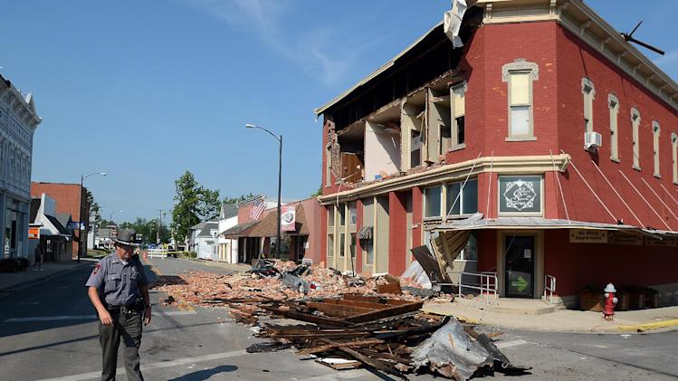 Police chief, Nick Gilgenbauch walks past a brick wall Monday, July 2, 2012, which fell Friday from the second story of the Christie's on the Square store in Columbus Grove, Ohio, and crushed, two vehicles parked in front. A  structural engineer is in Columbus Grove, Ohio on Monday to survey damage.  (AP Photo/The Lima News, Craig J. Orosz)  MANDATORY CREDIT
