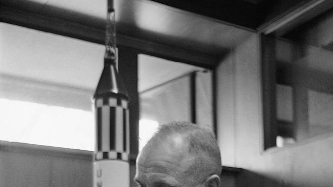 FILE - In this Feb. 8, 1963 file photo, astronaut John Glenn sits with models of the Mercury spacecraft atop its launch rocket and a lunar module, representing the past and the future of space exploration as he talks about the first anniversary of his historic flight. (AP Photo/Ed Kolenovsky, File)