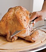 4. Using a carving fork to hold the wing steady, make a deep, horizontal cut above the wing joint.