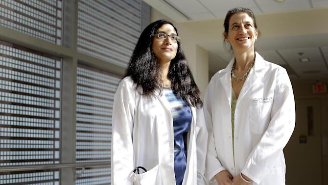 In this photo taken Aug. 21, 2012, Dr. Tara Palmore, deputy hospital epidemiologist at the National Institutes of Health Clinical Center, left, and Dr. Julie Segre, a geneticist with the National Human Genome Research Institute, pose at the NIH Clinical Center in Bethesda, Md. Last year a deadly superbug spread through the nation's leading research hospital, killing six patients before it could be stopped. Scientists at the National Institutes of Health hospital in Bethesda, Md., scrubbed with bleach, locked down patients and even ripped out plumbing. In the end, it took gene detectives analyzing the germ's DNA to trace it to its source. It came from a New York City patient who was admitted for a medical study. (AP Photo/Patrick Semansky)