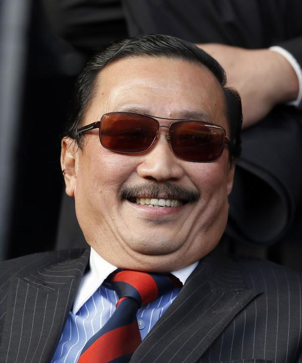 Cardiff City's owner Tan sits in the stands before their English Premier League soccer match against Liverpool at Anfield in Liverpool