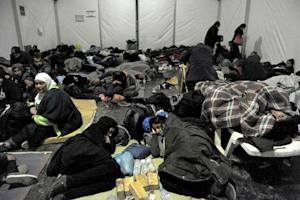 Refugees and migrants rest inside a tent at a camp, …