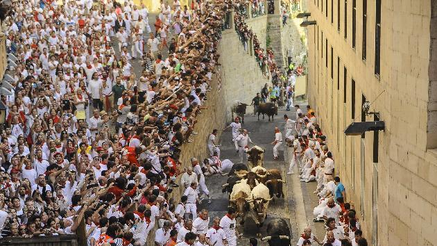 People watch participants run ahead of ''Jandilla'' fighting bulls from Santo Domingo street during the running of the bulls at the San Fermin Festival, in Pamplona, Spain, Tuesday, July 7, 2015. Revelers from around the world arrive to Pamplona every year to take part in some of the eight days of the running of the bulls. (AP Photo/Alvaro Barrientos)