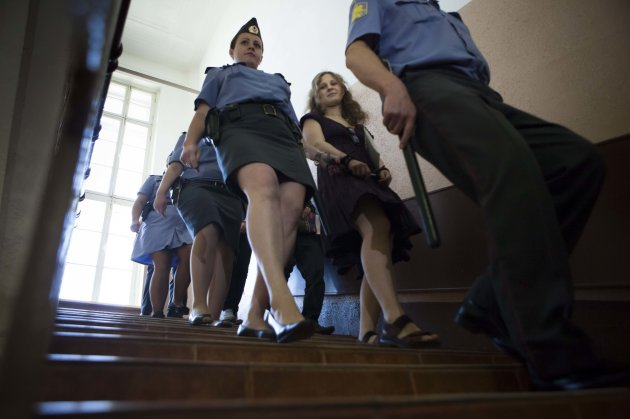 Feminist punk group Pussy Riot member Maria Alekhina, escorted to a court room in Moscow, Russia, Wednesday, Aug. 8, 2012. Prosecutors on Tuesday called for three-year prison sentences for feminist pu