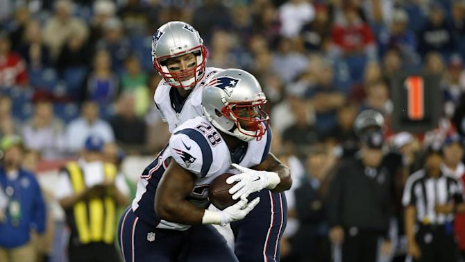 New England Patriots quarterback Tom Brady, rear, hands off to New England Patriots running back James White in the first quarter of an NFL football game against the Philadelphia Eagles Friday, Aug. 15, 2014, in Foxborough, Mass. (AP Photo/Elise Amendola)