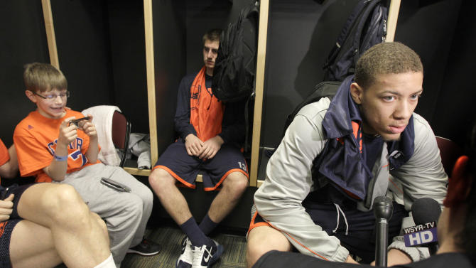 While Brandon Triche, right, of Syracuse talks with reporters, teammate Griffin Hoffmann sits in his locker and Griff Hopkins, son of team assistant coach Mike Hopkins, plays a hand held game  in the locker room after practice for an East Regional third round game in the NCAA college basketball tournament in Cleveland on Saturday, March 19, 2011.  Syracuse will face Marquette on Sunday.  (AP Photo/Amy Sancetta)
