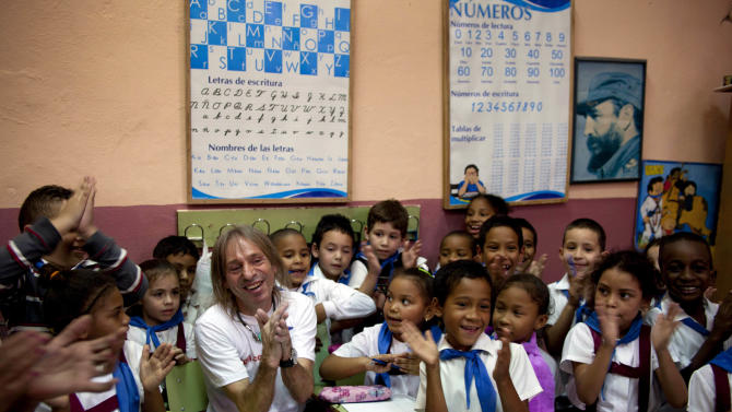 Schoolchildren pose for photos with French daredevil Alain Robert after he climbed the exterior their Angela Landa elementary school building without using ropes or a safety net in Old Havana, Cuba, Tuesday, Feb. 5, 2013. The 50-year-old Robert took 15 minutes to ascend the three stories of the graceful stone building, which offered little in the way of hand- and footholds. Robert has scaled the planet's loftiest skyscrapers from the Empire State Building to Dubai's Burj Khalifa, the world's tallest.  (AP Photo/Ramon Espinosa)
