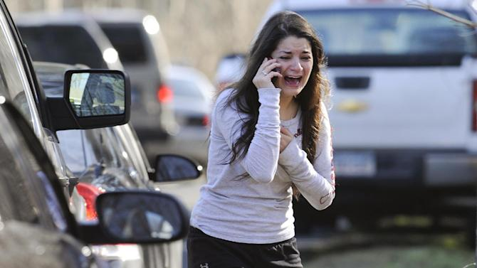 A woman waits to hear about her sister, a teacher, following a shooting at the Sandy Hook Elementary School in Newtown, Conn. where authorities say a gunman opened fire, leaving 27 people dead, including 20 children, Friday, Dec. 14, 2012. (AP Photo/Jessica Hill)