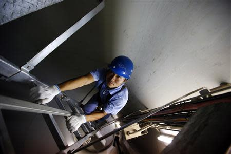 A worker inspects the interior of a wind turbine used to generate electricity, at a wind farm in Guazhou, 950km northwest of Lanzhou, Gansu Province