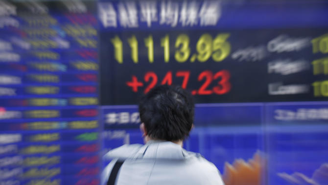 A man looks at the electronic stock board of a securities firm in Tokyo Wednesday, Jan. 30, 2013, as Japan's Nikkei surged 247.23 points, or 2.28 percent to 11,113.95, its highest level since April, 2010. Asian stock markets rose Wednesday after strong U.S. corporate earnings outweighed sagging consumer confidence. (AP Photo/Itsuo Inouye)