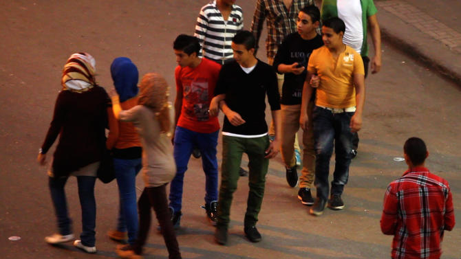 """In this undated image made from video released by the producers of """"Awel el Kheit"""" or """"the Thread"""" which airs on the private TV station ONTV, a group of young men harass three girls in Cairo, Egypt, during a segment of an investigative story on sexual harassment. While not new to Egypt's conservative society, sexual harassment has grown increasingly violent and visible in the nation, which has an embattled police force and an absence of legislation to address it. Egyptian law defines and criminalizes assault, but not sexual harassment.(AP Photo)"""