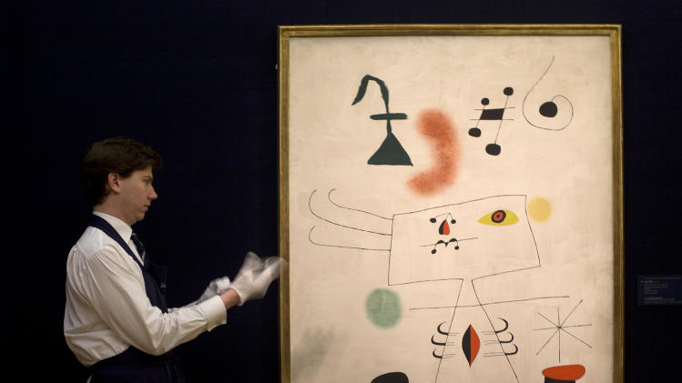 A Sotheby's employee poses for photographers as he puts on his white gloves standing next to a work by Joan Miro entitled 'Femme revant de l'evasion' during a press preview at Sotheby's auction house in London, Thursday, Jan. 31, 2013. The work is estimated to sell for some  8-12 million pounds (US$ 12.8-19.2 million, euro 9.9-14.8 million) when sold at auction on Feb. 5, in London. (AP Photo/Alastair Grant)