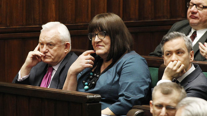 """Poland's first openly gay lawmaker, Robert Biedron, right, and first transsexual lawmaker, Anna Grodzka, center, took seats in the front bench of the parliament in Warsaw, Poland, Wednesday, March 6, 2013 to protest recent anti-gay remarks by former President Lech Walesa. Biedron and Grodzka usually sit in the third row, but their parliamentary floor moved them to the prestigious front row in a sign of support for them. Walesa said last week that gays belong in the back rows of Parliament, or even """"behind the wall."""" Sitting at left is Leszek Miller. (AP Photo/Czarek Sokolowski)"""