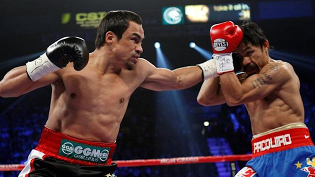 Juan Manuel Marquez (L) of Mexico fights Manny Pacquiao of the Philippines during their WBO welterweight fight at the MGM Grand Garden Arena in Las Vegas, Nevada November 12, 2011