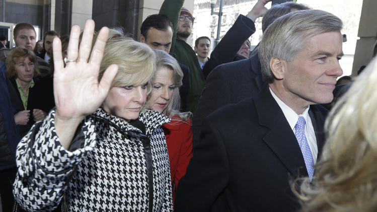 FILE - In this Friday, Jan. 24, 2014 file photo, Former Virginia Gov. Bob McDonnell, right, and his wife, Maureen, center, behind McDonnell, are surrounded by family and supporters as they leave Federal court in Richmond, Va. The former first lady of Virginia and her husband, former Gov. Bob McConnell, have been indicted on several counts of trading on their influence to enrich themselves and family members.(AP Photo/Steve Helber, File)