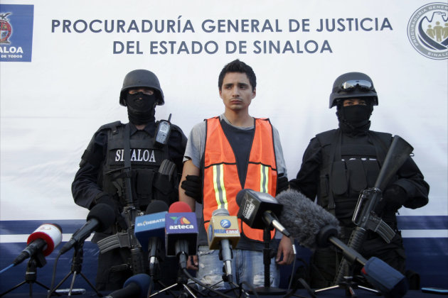 """Jose Ramon Acosta Quintero, aka """"El Ray"""", is escorted by soldiers during his presentation to the press in Mazatlan, Mexico, Saturday, Jan. 28, 2012. Acosta Quintero is accused by state authorities of being the man responsible in the brutal beating of Sheila Nabb, 37, a Canadian woman at a five-star resort in Mazatlan. Authorities are trying to find out whether Quintero was involved in other attacks on tourists, according to the Sinaloa state"""
