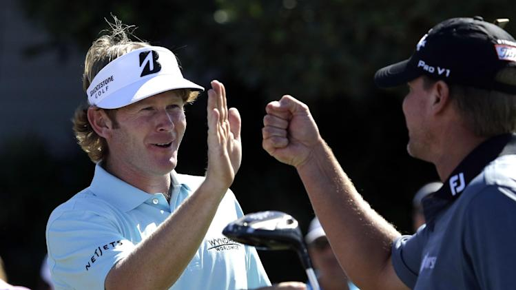 Brandt Snedeker, left, and Steve Stricker high-five and fist-bump as they prepare to tee off on the first hole during the first round at the Tournament of Champions PGA golf tournament on Sunday, Jan. 6, 2013, in Kapalua, Hawaii. Before the pair could start, play was suspended because of wind. (AP Photo/Elaine Thompson)