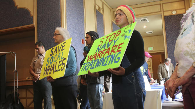 Demonstrators hold signs stating their position against US Navy training exercises off the California Coast, during a California Costal Commission meeting Friday, March 8, 2013 in San Diego. The U.S. Navy opposes state restrictions on an explosives and sonar training program off the Southern California coast that critics fear will threaten whales and other sea mammals, state regulators were told Friday. (AP Photo/Lenny Ignelzi)