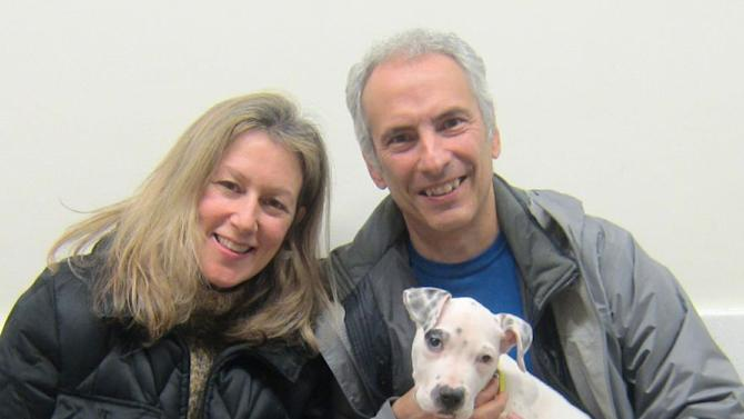 In this Jan. 16, 2013 photo provided by the American Society for Prevention of Cruelty to Animals, Pamela Harris and Joseph Villari pose with Pinky, their three month old pit bull mix, who they named Opal after adopting her, at the ASPCA's Adoption Center in New York. In order to be prepared for dog ownership, experts say you need to examine your lifestyle, home and finances. Then, you need to find the right match.  (AP Photo/ASPCA)