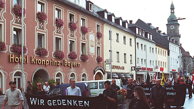 "FILE - The Aug. 17, 2002 file photo shows Neo-Nazis during a rally in memory of Adolf Hitler's deputy Rudolf Hess in Hess' Bavarian hometown of Wunsiedel, southern Germany. The small town in Germany that was a pilgrimage site for neo-Nazis is now welcoming jobless foreigners with open arms. A dozen Spaniards affected by record unemployment in their home country made their way last year to Wunsiedel on the German-Czech border. The town, nestled in the north Bavarian hills mountains, was best known as the burial place of Adolf Hitler's deputy Rudolf Hess, drawing annual far-right marches until authorities put a stop to them in 2005. Now Wunsiedel has become an example of how Germans and Spaniards can help jobless southern Europeans find work in the north, where low birthrates and continued economic prosperity have created a labor shortage on a continent struggling with recession and unemployment, especially among its youth. Banner reads: ""We commemorate Rudolf Hess."" (AP Photo/Udo Bartsch)"