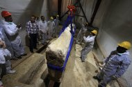 In this Thursday, June 23, 2011 file photo, an Egyptian and Japanese team of scientists use a pulley system to lift the first of 41 16-ton limestone slabs to reveal fragments of the ancient ship of King Khufu next to the Great Pyramid of Giza, Egypt. Archaeologists began a second-phase of restoration work on a 4,500-year-old wooden boat found next to the Great Pyramid of Giza, one of Egypt's main tourist attractions. (AP Photo/Khalil Hamra, File)