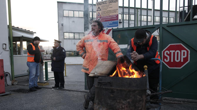 Striking Metro worker stand next to the fire at the entrance of subway train depot in Athens, on Friday, Jan. 25, 2013. Riot police in Greece have stormed a subway train depot in Athens, where striking workers had barricaded themselves. The government had issued an emergency order to force them to end an eight-day strike in an escalating standoff over austerity measures. Police broke through the gates and removed dozens of strikers in Friday's pre-dawn raid. (AP Photo/Petros Giannakouris)