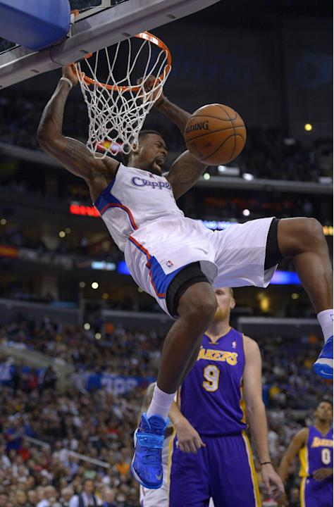 Los Angeles Clippers forward Jared Dudley, top, dunks as Los Angeles Lakers center Chris Kaman looks on during the first half of an NBA basketball game, Friday, Jan. 10, 2014, in Los Angeles. (AP Phot