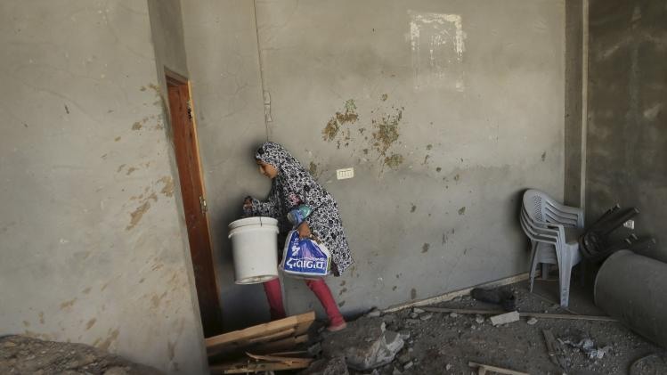 A Palestinian girl carries her belongings from her family's damaged house in the Shejaia neighbourhood, which witnesses said was heavily hit by Israeli shelling and air strikes during an Israeli offensive, in Gaza City