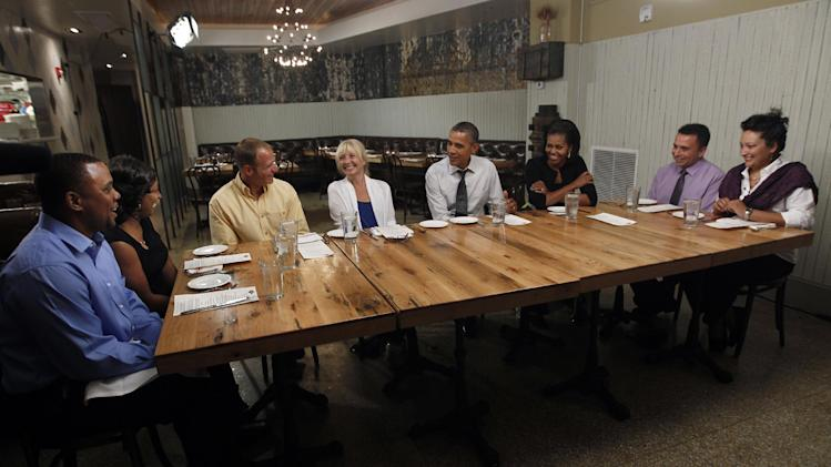 President Barack Obama and first lady Michelle Obama have dinner at a Mintwood Place restaurant in Adams Morgan neighborhood in Washington with winners of a campaign contest, Monday, Aug. 20, 2012. (AP Photo/Pablo Martinez Monsivais)