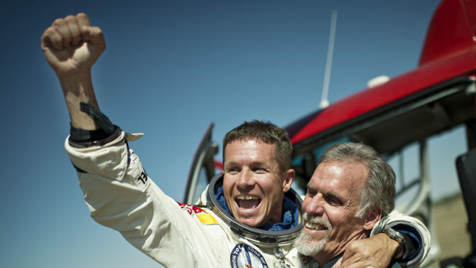 In this photo provided by Red Bull Stratos, pilot Felix Baumgartner of Austria and Technical Project Director Art Thompson, celebrate after successfully completing the final manned flight for Red Bull Stratos in Roswell, N.M., Sunday, October 14, 2012. Baumgartner came down safely in the eastern New Mexico desert minutes about nine minutes after jumping from his capsule 128,097 feet, or roughly 24 miles, above Earth. (AP Photo/Red Bull Stratos, Joerg Mitter)