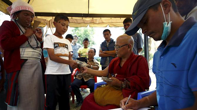 A monk distributes money donated to the earthquake victims from Langtang district at a Tibetan monastery in Kathmandu