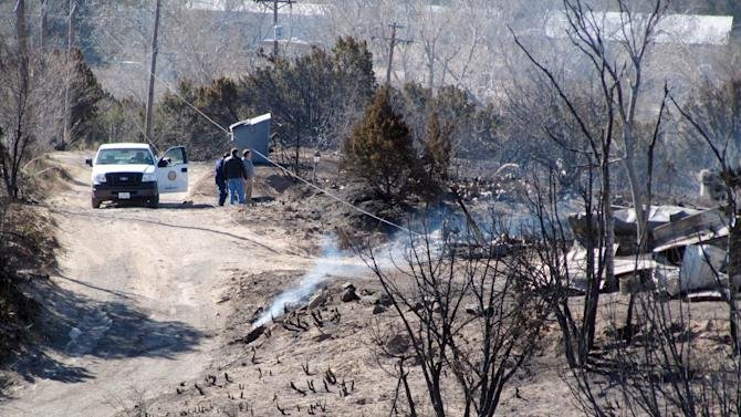 Fire officials check smoldering hot spots and check damage in Lake Tanglewood,  a small community southeast of Amarillo, Texas,  where several homes were destroyed by wildfires  are seen Monday, Feb. 28, 2011. Firefighters have contained wind-driven wildfires that burned about 121,000 acres in West Texas and the Panhandle, but there is a danger of blazes breaking out in the south. (AP Photo/Betsy Blaney)