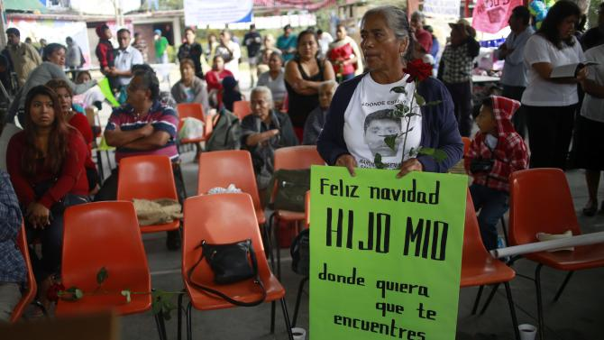 A mother of one of the 43 missing students on September 26 holds a sign before a mass officiated by Apostolic Nuncio to Mexico Christopher Pierre in the Ayotzinapa Teacher Training College Raul Isidro Burgos, on the outskirts of Chilpancingo, Guerrero