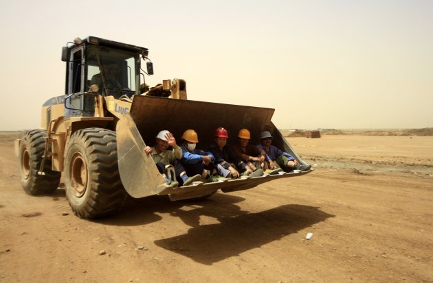 A bulldozer carries Chinese workers to the White Nile Sugar Factory in El Diwaym